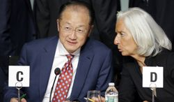 Jim Yong Kim, left, president, World Bank Group, and Christine Lagarde, International Monetary Fund (IMF) Managing Director talk before a meeting of the Development Committee during the World Bank/IMF Annual Meetings at IMF headquarters Saturday, Oct. 12, 2013, in Washington. (AP Photo/Alex Brandon)