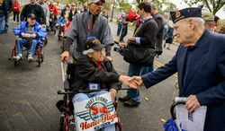 Mike Lauriente (right) of Howard County, Md., greets fellow World War II veteran Dale Nakken, who flew from Puget Sound, Wash., as they make their way to the World War II Memorial for the Million Vet March against the closure of the monument. Story, A12. (Andrew Harnik/The Washington Times)