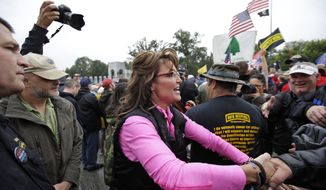 """Former Alaska Gov. Sarah Palin, arrives for a rally at the World War II Memorial in Washington Sunday, Oct. 13, 2013, to protest, as she said, how politicians used """"your hard-earned tax money to barricade the memorials"""" during the federal government shutdown. She called it a """"slimdown,"""" saying it only halted a small part of the """"bloated"""" government. The Memorial has been closed to the public since the shutdown. (AP Photo/Alex Brandon)"""