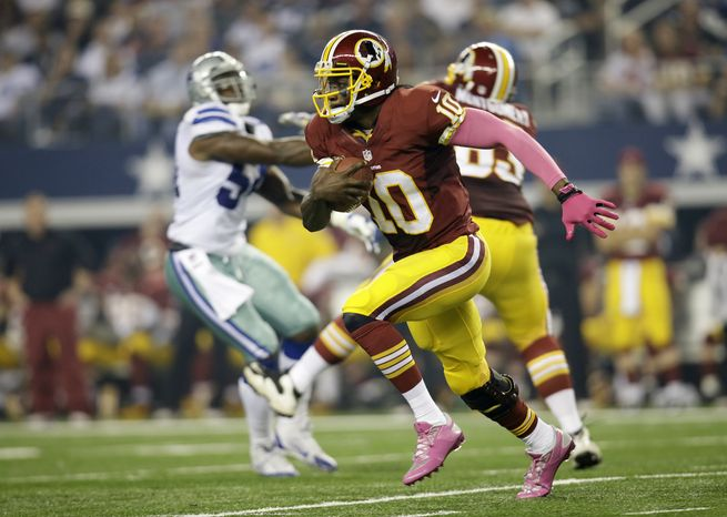 Washington Redskins quarterback Robert Griffin III (10) runs with the ball in the first half of an NFL football game against the Dallas Cowboys Sunday, Oct. 13, 2013, in Arlington, Texas. (AP Photo/Tim Sharp)