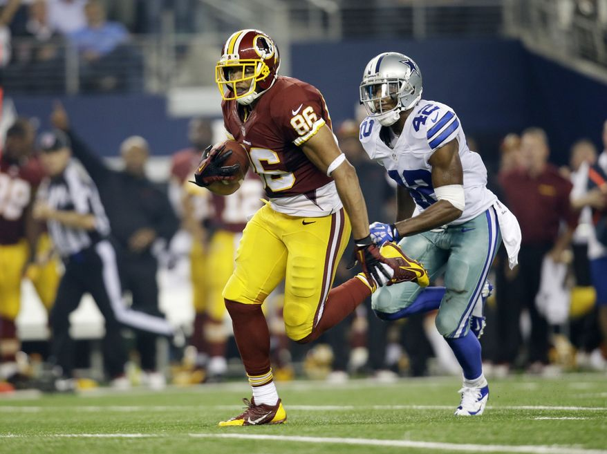 Washington Redskins tight end Jordan Reed (86) carries the ball as Dallas Cowboys free safety Barry Church (42) defends in the first half of an NFL football game, Sunday, Oct. 13, 2013, in Arlington, Texas. (AP Photo/Tim Sharp)