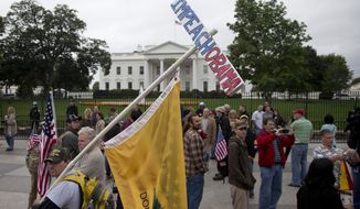 "A man, who asked to be identified only as ""Frank"", carries and ""Impeach Obama"" sign while protesting with others outside the White House in Washington Sunday, Oct. 13, 2013, as the partial government shutdown enters its third week.  (AP Photo/Carolyn Kaster)"