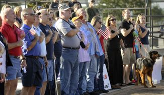 Veterans and supporters sing the National Anthem at a rally to back veterans Sunday Oct. 13, 2013 at the Veterans Memorial Wall in Jacksonville, Florida. The rally was held at the same time as other rallies nationwide and the Million Vet March on the Memorials in Washington, D. C. to protest the closing of memorials that are normally open at all times and have no staff to guard them under normal circumstances.  (AP Photo/The Florida Times-Union, Will Dickey)