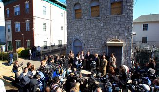 Newark Mayor Cory Booker (center, at microphones), stands in front of fire-damaged 433 Hawthorne Ave., next to the place he calls home (left), as he talks about rescuing a neighbor. A report on a conservative website that he doesn't actually live there has his Republican challenger for the U.S. Senate asking him to come clean on where he lives. The special election is Wednesday. (Associated Press photographs)