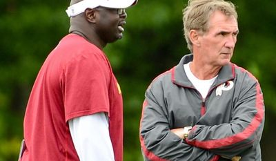 Washington Redskins head coach Mike Shanahan, right, talks with special teams coach Keith Burns, left, during a NFL football organized team activity at Redskins Park, Ashburn, Va., Thursday, June 6, 2013. (Andrew Harnik/The Washington Times)