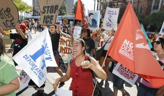 """A protester yells as she joins about 250 people as they march to the U.S. Immigrations and Customs Enforcement office with a goal of stopping future deportations on Monday Oct. 14, 2013, in Phoenix.  The protesters chanted """"no more deportations"""" and """"shut down ICE."""" (AP Photo/Ross D. Franklin)"""