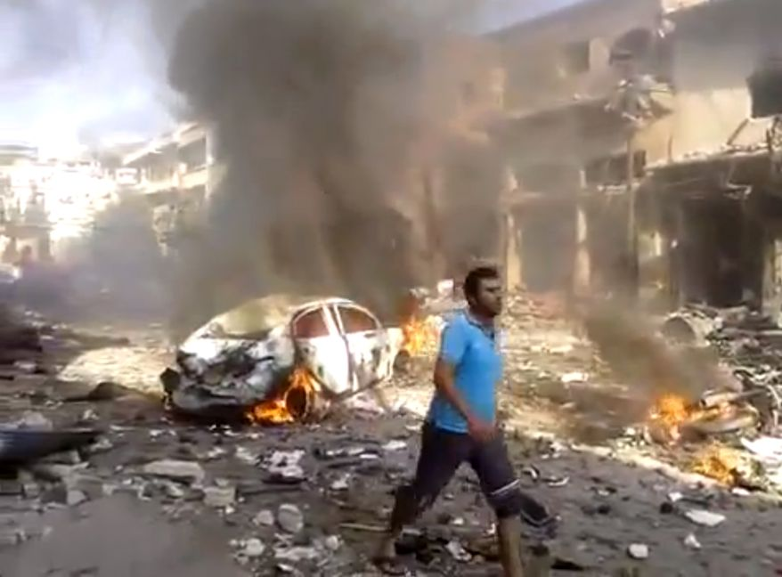 This image made from citizen journalist video posted by the Shaam News Network, which is consistent with other AP reporting, shows the aftermath of a car bomb attack on a market in the town of Darkoush in Idlib province, Monday, Oct. 14, 2013. (AP Photo/Shaam News Network via AP video)