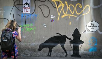 ** FILE ** Secretive British artist Banksy created a piece featuring a dog and a fire hydrant on 24th Street, near Sixth Avenue in New York, Oct. 4, 2013. (AP Photo/Bebeto Matthews, File)