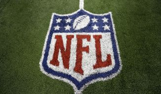 An NFL logo marks the turf on the field after a football game between the Washington Redskins and Dallas Cowboys Sunday, Oct. 13, 2013, in Arlington, Texas. (AP Photo/LM Otero)