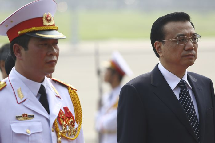 Chinese Premier Li Keqiang, right, attends a wreath laying ceremony at the mausoleum of former Communist leader Ho Chi Minh in Hanoi, Vietnam Monday, Oct. 14, 2013. Li is in the country to tie up the cooperation between the two neighbors. (AP Photo/Na Son Nguyen, Pool)