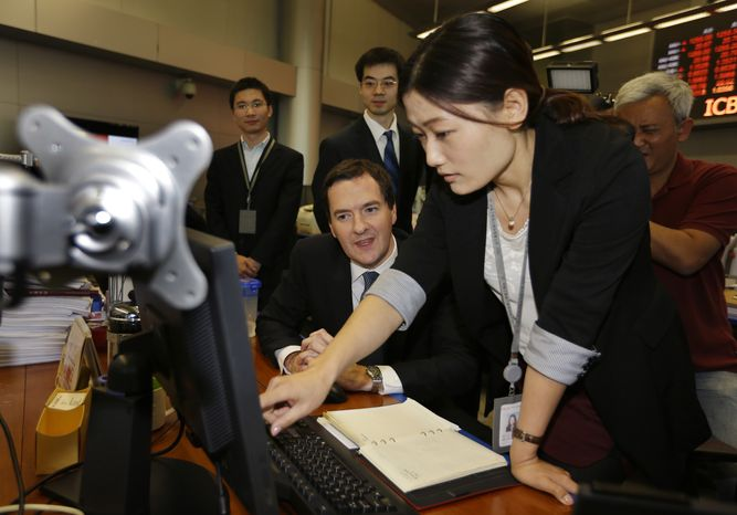 ** FILE ** Britain's Chancellor of the Exchequer George Osborne, left, looks at a trading screen as he listens to a staff member of Industrial and Commercial Bank of China Ltd (ICBC) at a trading center during his visit to the ICBC headquarters in Beijing Tuesday, Oct. 15, 2013. (AP Photo/Jason Lee, Pool)