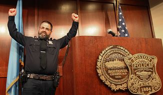 Boston Police Officer Steve Horgan, raises his hands as he poses for a photograph during a news conference on Tuesday, Oct. 15, 2013 in Boston. Horgan says he's humbled by the attention he's received since photographs of him raising his arms in jubilation after the Boston Red Sox hit a grand slam against the Detroit Tigers appeared in newspapers and on the Internet. The photos show Horgan's arms raised in the same frame as the upturned legs of Tigers outfielder Torii Hunter as he tumbles into the Fenway Park bullpen, where Horgan was working a security detail. David Ortiz's grand slam tied Sunday's game 5-5, and the Red Sox went on to a 6-5 victory.  (AP Photo/The Boston Globe, Suzanne Kreiter)  BOSTON HERALD OUT, QUINCY OUT; NO SALES