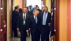 Senate Minority Leader Mitch McConnell, Kentucky Republican, walks to the floor from a closed-door meeting with Republican senators at the Capitol  on Wednesday. Mr. McConnell and his Democratic counterpart, Senate Majority Leader Harry Reid, Nevada Democrat, reached last-minute agreement to avert a possible default on government debt. (Associated press photographs)