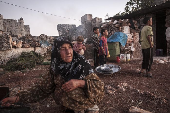 A displaced Syrian woman cooks a meal as children play in the sunset near Kafer Rouma in ancient ruins used as temporary shelter by families who have fled the heavy fighting and shelling in the Idlib provincial countryside of Syria. (AP Photo/Narciso Contreras)