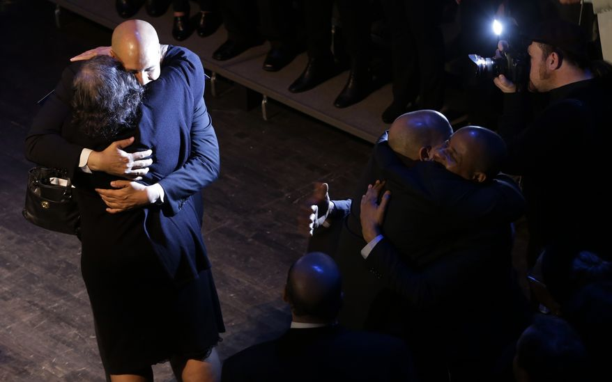 Newark Mayor Cory Booker, top left, hugs his mother Carolyn Booker after giving his victory speech during an election night party, Wednesday, Oct. 16, 2013, in Newark, N.J. Booker and Republican Steve Lonegan faced off during a special election to fill the U.S. Senate seat left vacant by the death of Sen. Frank Lautenberg. (AP Photo/Julio Cortez)