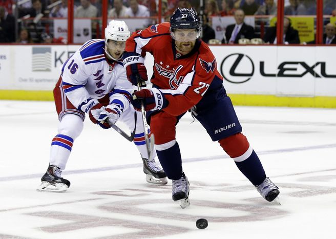 Washington Capitals defenseman Karl Alzner, right, skates with the puck with New York Rangers center Derick Brassard, behind, in the first period of an NHL hockey game, Wednesday, Oct. 16, 2013, in Washington. (AP Photo