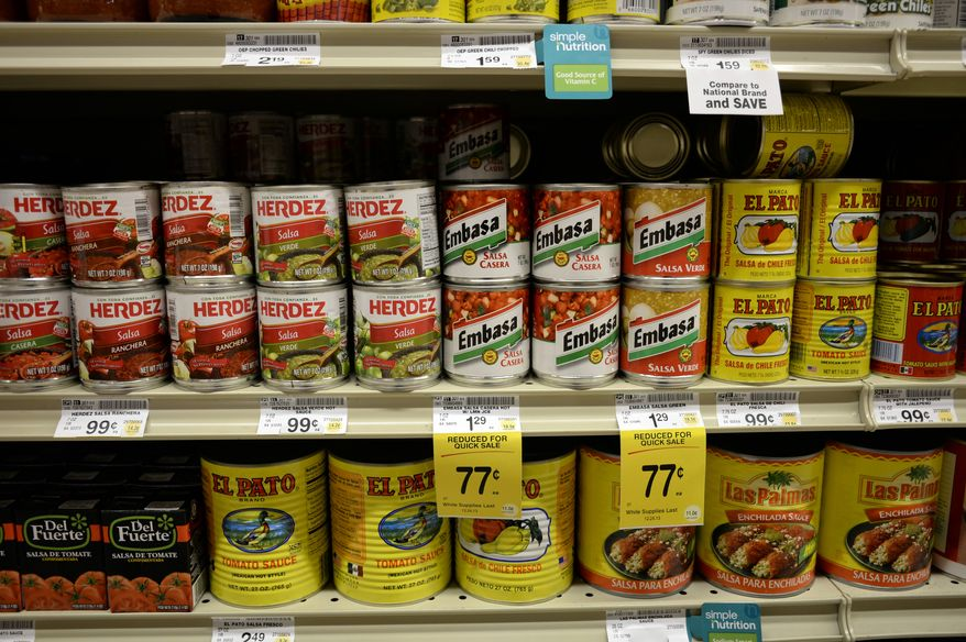 """Salsas and other items are seen in the International food aisle of a grocery store Wednesday, Oct. 16, 2013, in Washington. These days, tortillas outsell burger and hot dog buns; sales of tortilla chips trump potato chips; and tacos and burritos have become so ubiquitously """"American,"""" most people don't even consider them ethnic. (AP Photo/Alex Brandon)"""