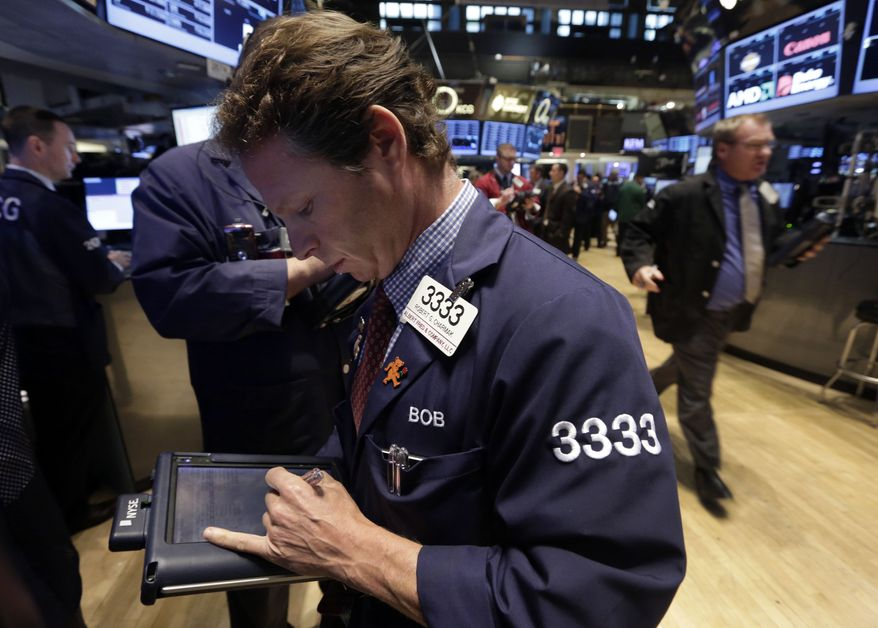 Trader Robert Charmak, left, works on the floor of the New York Stock Exchange Tuesday, Oct. 15, 2013. World stock markets fluctuated between gains and losses Wednesday Oct. 16, 2013 as a deadline for divided U.S. lawmakers to agree on a higher government borrowing limit drew ever closer. (AP Photo/Richard Drew)