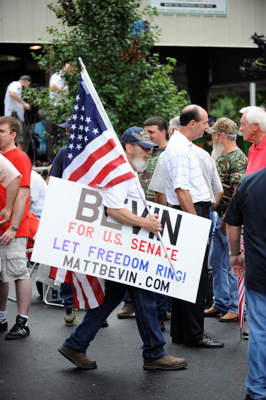 Tom Barbour of New Haven, Ky., carries a sign in support of Matt Bevin during the Fancy Farm picnic in Kentucky in August. Mr. Bevin, a businessman, praised Sen. Ted Cruz, Texas Republican, as the new face of the conservative movement and blasted Senate Minority Leader Mitch McConnell, who wrote the final debt deal with his Democratic counterpart Majority Leader Harry Reid. (Associated Press)