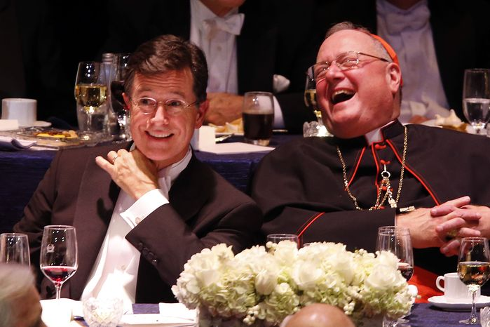Keynote speaker Stephen Colbert, left, and Cardinal Timothy Dolan laugh during the Alfred E. Smith Memorial Foundation Dinner, a charity gala organized by the Archdiocese of New York, at the Waldorf-Astoria hotel, Thursday, Oct. 17, 2013, in New York. (AP Photo/Jason DeCrow)