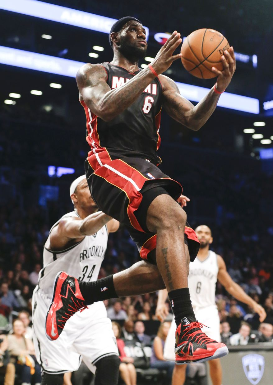 Miami Heat's LeBron James (6) drives past Brooklyn Nets' Paul Pierce (34) during the second half of an NBA basketball game Thursday, Oct. 17, 2013 in New York. The Nets won the game 86-62.  (AP Photo/Frank Franklin II)