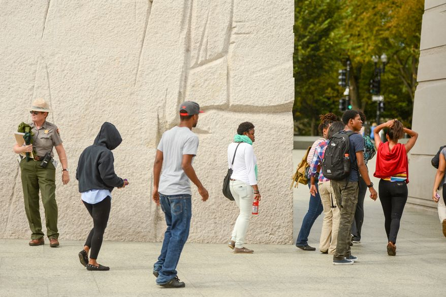 U.S. Park Ranger Jenna Skogg, left, stands at the Martin Luther King Jr. Memorial ready to assist  tourists navigate the National Mall on the first day monuments reopen after the government shutdown, Washington, D.C., Thursday, October 17, 2013. (Andrew Harnik/The Washington Times)