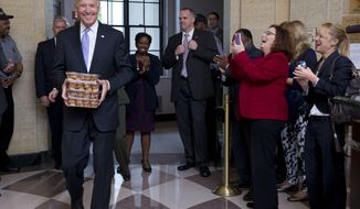 Vice President Joseph R. Biden (left) greets Environmental Protection Agency workers with muffins as they return to work at the William Jefferson Clinton Federal Building in Washington on Thursday, Oct. 17, 2013, after a 16-day partial government shutdown. (AP Photo/Jacquelyn Martin)