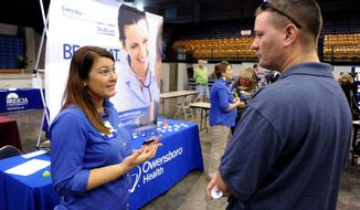 Registered nurse Salanda Bowman (left) talks with part-time Kentucky Wesleyan College student Jason Ward of Whitesville, Ky., about job openings at the Owensboro Health Regional Hospital during a job fair in the Owensboro Sports Center in Owensboro, Ky., on Tuesday, Oct. 1, 2013. (AP Photo/The Messenger-Inquirer, Gary Emord-Netzley)