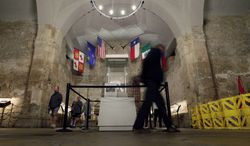 "FILE - In this Feb. 13, 2013, file photo, visitors walk past a custom case that will house Texas hero William Barret Travis' famed ""Victory of Death"" letter at the Alamo, in San Antonio. The Texas General Land Office, which took control of the Alamo in 2011, approved a gun rights rally for Saturday, Oct. 19, 2013, breaking with tradition that had kept demonstrations off the hallowed ground. Land Commissioner Jerry Patterson, who signed off on the event and was scheduled to speak at the rally, says he now plans to develop a policy and permitting process. (AP Photo/Eric Gay, File)"