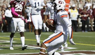 Auburn quarterback Nick Marshall (14) scores against Texas A&M in the first quarter during an NCAA college football game Saturday, Oct. 19, 2013, in College Station, Texas. (AP Photo/Bob Levey)