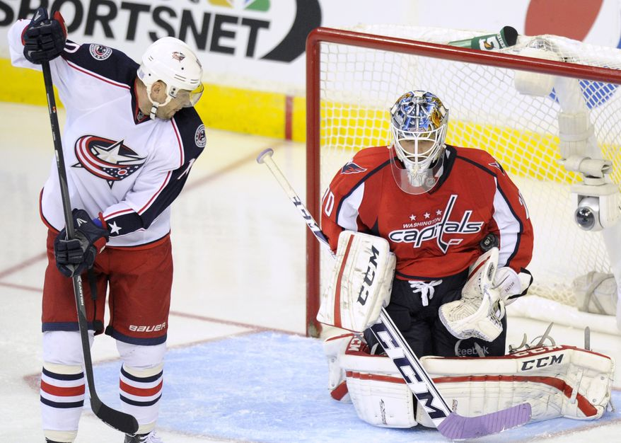 Washington Capitals goalie Braden Holtby (70) stops the puck as Columbus Blue Jackets right wing Marian Gaborik, left,  of Slovakia, looks on during the third period an NHL hockey game, Saturday, Oct. 19, 2013, in Washington. The Capitals won 4-1. (AP Photo/Nick Wass)