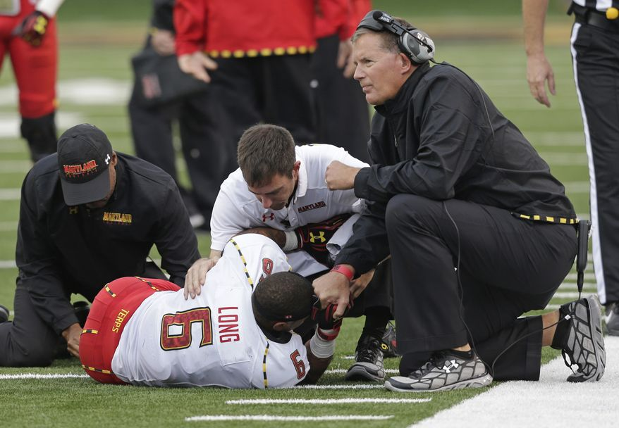 Maryland coach Randy Edsall, right, holds the hand of Deon Long (6) as Long is examined by trainers after being injured in the first half of an NCAA college football game against Wake Forest in Winston-Salem, N.C., Saturday, Oct. 19, 2013. (AP Photo/Chuck Burton)