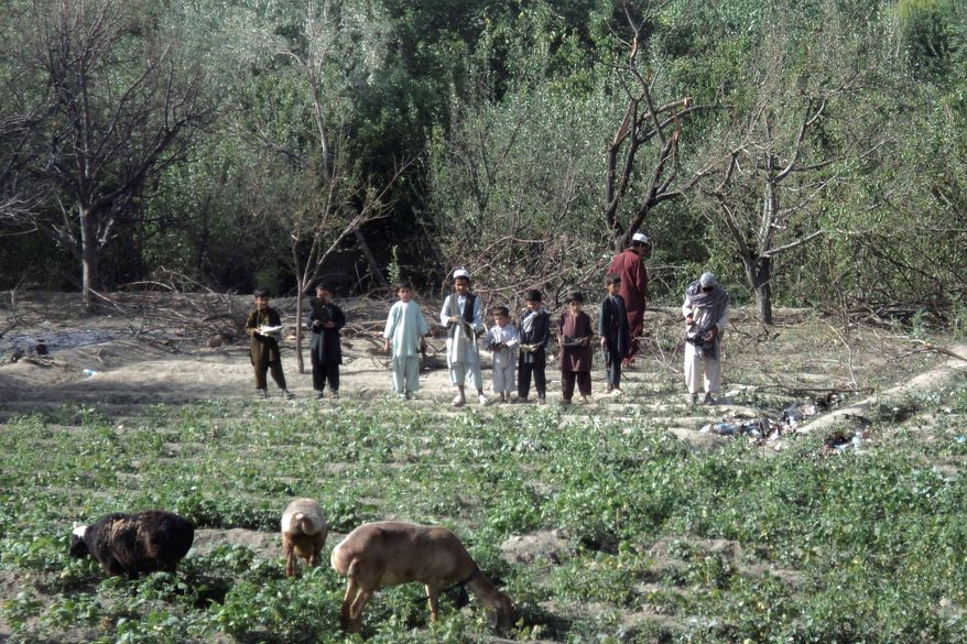 """Afghan children visit the site where a Chinook was shot down in 2011. Wreckage was scattered on both sides of a river in the Tangi Valley. """"The CH-47 was used in a completely inappropriate manner given its design,"""" a special operations officer said. (Associated Press)"""