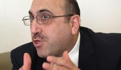Rami Abdurrahman, head of the Britain-based Syrian Observatory for Human Rights, gestures during an interview with The Associated Press in Coventry, England, on Wednesday, Oct. 10, 2013. (AP Photo/Raphael Satter)