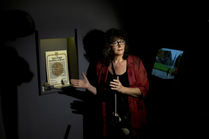 "Irena Steinfeldt, an official at Israel's Yad Vashem Holocaust memorial, shows a certificate recognizing Dr. Mohamed Helmy, an Egyptian physician in Berlin, as ""Righteous Among the Nations"" for saving a Jewish family during the Holocaust, in Jerusalem on Monday, Sept. 30, 2013. (AP Photo/Sebastian Scheiner)"