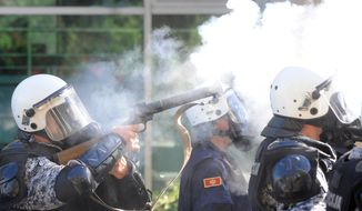 A police officer fires tear gas against dozens of rock-throwing opponents of a gay pride march in Podgorica, Montenegro, on Sunday, Oct. 20, 2013. (AP Photo/Risto Bozovic)