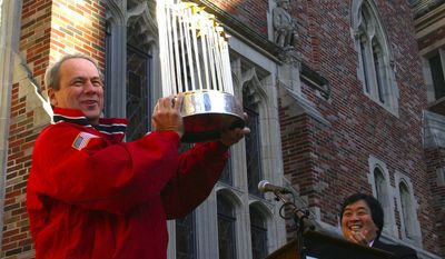 Larry Lucchino, president and CEO of the Boston Red Sox holds the World Series trophy during a Red Sox rally at the Yale Law School Nov. 17, 2004 in New Haven, Conn.  Lucchino, a 1971 graduate of Yale, was accompanied by the Yale Law School Dean Harold Hongyu Koh, right.  (AP Photo/Michelle McLoughlin)