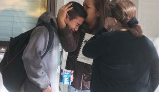 A  Sparks Middle School student cries after being released from Agnes Risley Elementary School, to which some students were evacuated, after a shooting at the middle school in Sparks, Nev., on Monday, Oct. 21, 2013. A  middle school student opened fire on campus just before the starting bell, wounding two boys and killing a staff member who was trying to protect other children, Sparks police said. The lone suspected gunman was also dead, though it's unclear whether the student committed suicide. (AP Photo/Kevin Clifford)