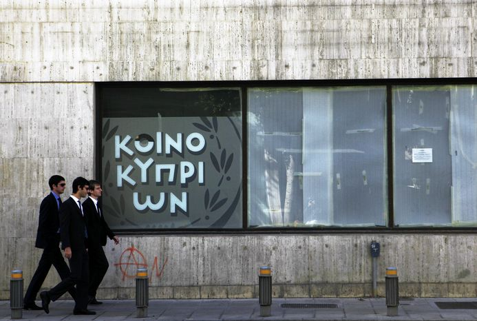 People walk past a closed and empty branch of the Bank of Cyprus in Nicosia, Cyprus, Monday, Oct. 21, 2013. Cyprus' finance minister says the budget deficit next year is forecast to beat the target outlined in the terms of the country's bailout. Cyprus was granted in March a 10 billion-euro ($13.68 billion) loan to avoid bankruptcy, but forced uninsured savers in the country's two biggest banks to take major losses on their savings. Authorities also imposed controls on the flow of capital to prevent a bank run. (AP Photo/Petros Karadjias)
