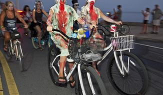 In this Sunday, Oct. 20, 2013 photo provided by the Florida Keys News Bureau, participants in the Zombie Bike Ride pedal on A1A next to the Atlantic Ocean in Key West, Fla. Thousands of costumed bicycle riders participated in the event. Key West's annual Fantasy Fest costuming and masking festival, that began Friday, Oct. 18, continues through Sunday, Oct. 27. (AP Photo/Florida Keys News Bureau, Rob O'Neal)