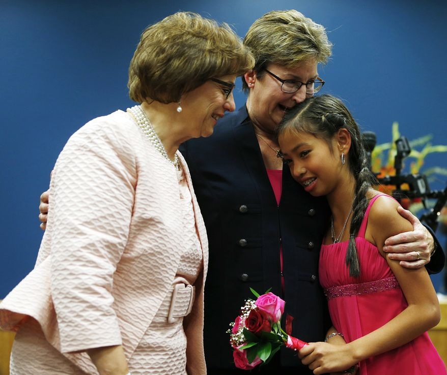Beth Asaro, left, and Joanne Schailey share a moment with their daughter Kate, 13, after they exchanged vows to become the first same-sex marriage in Lambertville, N.J., history at 12:01 a.m. Monday, Oct. 21, 2013 in Lambertville, N.J. Asaro and Schailey hold the distinction of being the first couple to enter into a civil union in the state, when that law took effect in 2007. (AP Photo/Rich Schultz)