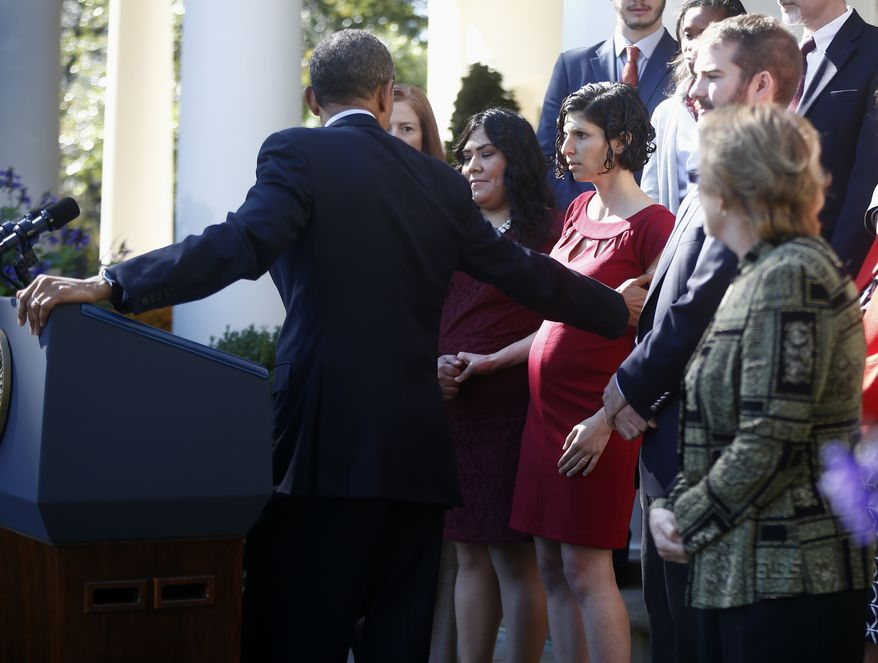 President Barack Obama reaches over to help Karmel Allison of San Diego who started to lose her balance while he was speaking in the Rose Garden of the White House in Washington, Monday, Oct. 21, 2013, on the initial rollout of the health care overhaul. The woman, who was standing with a group of supporters of the health care law, was helped away from the stage. Obama acknowledged that the widespread problems with his health care law's rollout are unacceptable, as the administration scrambles to fix the cascade of computer issues. (AP Photo/Charles Dharapak)