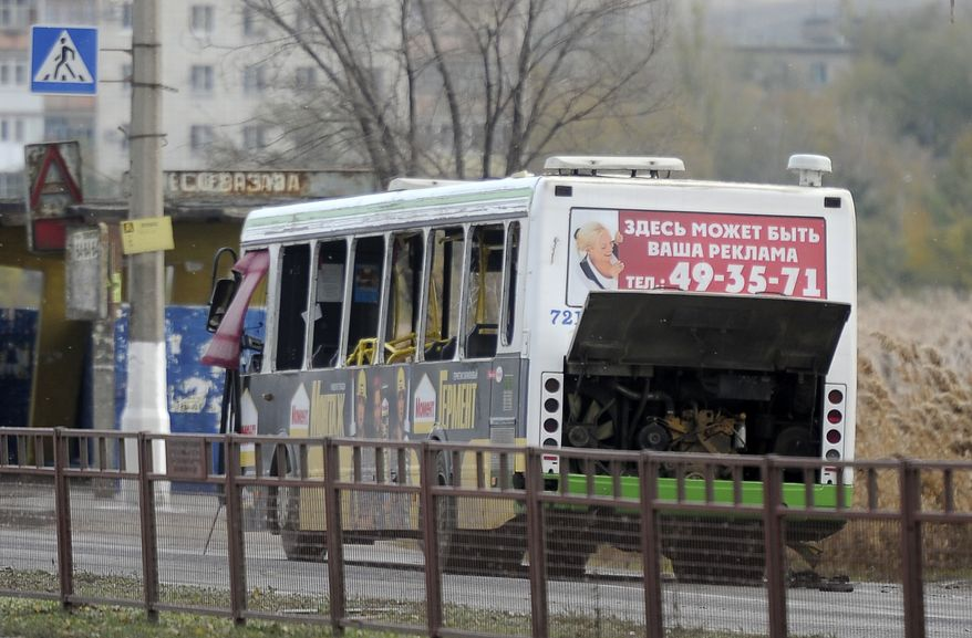 Experts examine a bus damaged by a bomb blast in Volgograd, Russia, on Monday, Oct. 21, 2013. (AP Photo/Sergei Ivanishin)