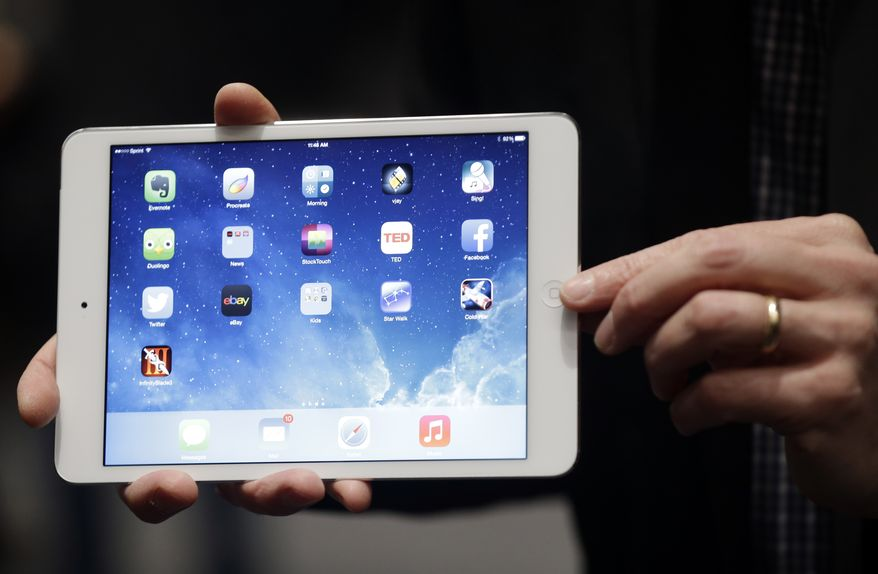 """An Apple employee demonstrates the new iPad Mini on Tuesday, Oct. 22, 2013, in San Francisco. Apple unveiled a new, thinner, lighter tablet called the """"iPad Air"""" and the iPad Mini with Retina Display, along with a slew of new Macs Tuesday at an event in San Francisco.  (AP Photo/Marcio Jose Sanchez)"""