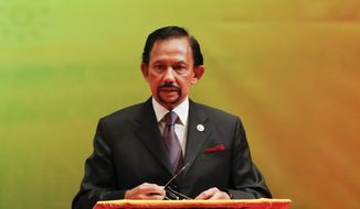 In this photo taken Thursday, Oct, 10, 2013, Brunei's Sultan Hassanal Bolkiah speaks during the closing ceremony and handover of the ASEAN Chairmanship to Myanmar in Bandar Seri Begawan. The Brunei's sultan has announced that a new Islamic criminal law that could include penalties like amputation for thefts and stoning for adultery will be enforced in six months. (AP Photo/Vincent Thian)