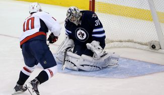 Washington Capitals' Martin Erat (10) scores the game-winning goal in a shootout against Winnipeg Jets' goaltender Ondrej Pavelec (31) during an NHL hockey game in Winnipeg, Manitoba, Tuesday, Oct. 22, 2013. The Capitals won 5-4 in a shootout. (AP Photo/The Canadian Press, Trevor Hagan)n