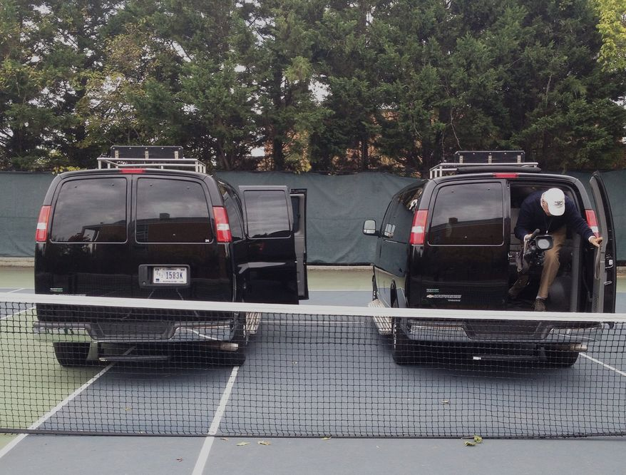 Press vans from the motorcade of President Obama park on the tennis courts of the Sidwell Friends School in Washington on Oct. 22, 2013. President Obama and first lady Michelle Obama are attending parent teacher meetings at the school where their daughters Sasha and Malia attend. (Associated Press) **FILE**