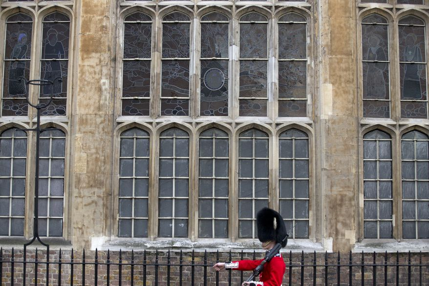 A Grenadier Guard marches past the stained glass windows of the Chapel Royal outside St James's Palace, in London, Wednesday, Oct. 23, 2013. Prince William and his wife Kate have asked seven people to be godparents to their son, Prince George, who will be christened at a major royal family gathering Wednesday, palace officials said.  Queen Elizabeth II and her husband Prince Philip plan to attend the christening Wednesday at the Chapel Royal at St. James's Palace, along with Prince Charles, his wife Camilla, Prince Harry and other royals. (AP Photo/Alastair Grant)