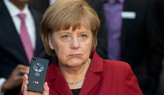 "FILE - The March 5, 2013 file photo shows German Chancellor Angela Merkel presenting a tap-proof mobile phone of Blackberry at a booth of Secusmart during the opening round tour of the world's largest computer expo CeBIT in Hannover. German Chancellor Angela Merkel complained to President Barack Obama on Wednesday, Oct. 23, 2013 after learning that U.S. intelligence may have targeted her mobile phone, and said that would be ""a serious breach of trust"" if confirmed, her government said.  (AP Photo/dpa, Julian Stratenschulte)"