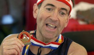 Former Arkansas Gov. Mike Huckabee shows his finisher's medal from the 2005 marathon. (associated press)